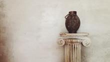 Ancient Amphora On A Marble Column. Background Grunge Plaster