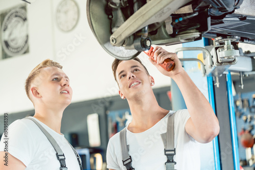 Photo Portrait of an experienced auto mechanic smiling while teaching an apprentice ab