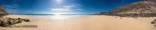 Panorama of the sandy sea beach with the sun