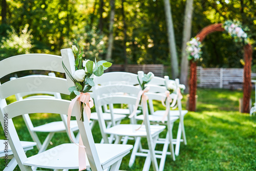 Fotografía  White fresh flowers with pink ribbon on wedding chair on each side of archway outroods; copy space