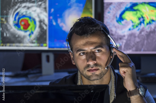 Leinwand Poster Meteorologist monitoring storms on his computer screens, close up shot