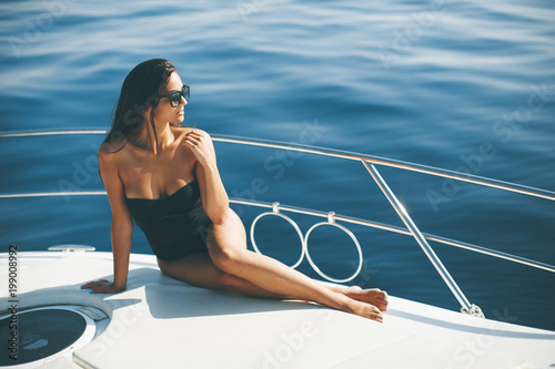 Leinwand Poster Young attractive woman poses on  luxury yacht floating on sea