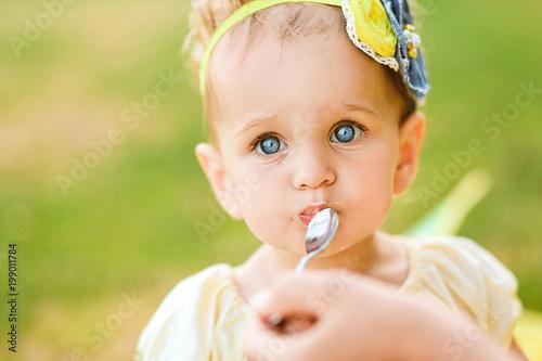 small blue eyed girl eats play outside Tablou Canvas