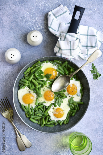 Healthy vegetarian breakfast : fried eggs and asparagus bean in a skillet.Top view.