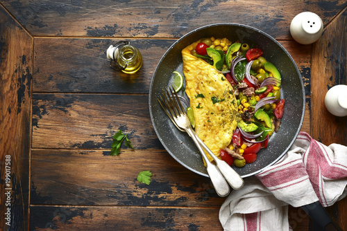 Omelette stuffed with vegetables in a black skillet for a breakfast.Top view with copy space.