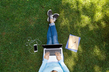 Top View Of Female Student Sitting In Park With Laptop