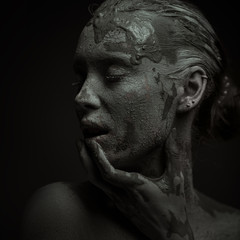 Statuesque woman in clay. Woman covered in clay.
