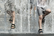 Two Boys Jumping Over Fountain Streams. Legs