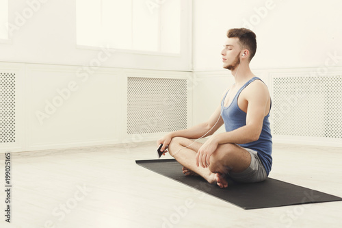 Poster Ecole de Yoga Man training yoga in lotus pose, copy space