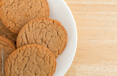 Tuinposter Koekjes Top close view of several brown sugar and cinnamon cookies on a plate atop a wood table.