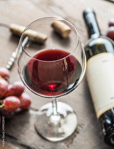 Fotografía  Wine glass, wine bottle and grapes on wooden background