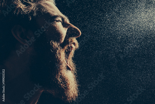 A bearded man angrily screams into a spray of water against a black background Fototapet