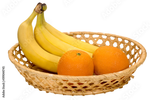 Fényképezés  three ripe banana and two oranges in a wicker plate