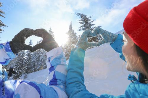 Fotobehang Wintersporten Lovely couple holding hands in shape of heart at snowy resort. Winter vacation