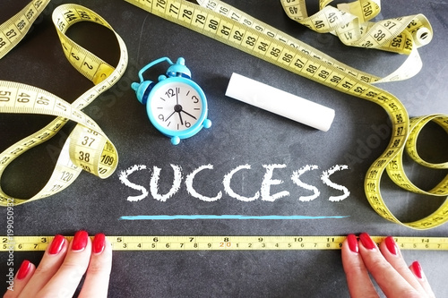 Success measurement concept with woman hands and yellow measurement tape on blac Canvas Print