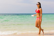 Smiling girl in red and pink bikini walking by the seashore with sunglasses and earphones connected to a mobile in the island of Koh Pha Ngan, Thailand. Young atractive woman enjoying free time