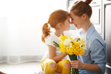 Fototapeta Kwiaty - happy mother's day! child daughter   gives mother a bouquet of flowers to narcissus and gift