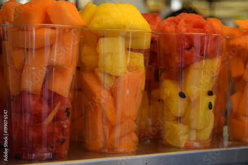 Fresh cut pineapple, cantaloupe and watermelon in tall plastic glasses on display at the market