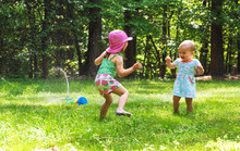 Happy Toddler Girls Playing In A Water Sprinkler Outside