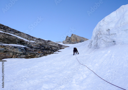 Fototapeta  mountain climber heading up a steep hanging glaicer around seracs in the Alps of