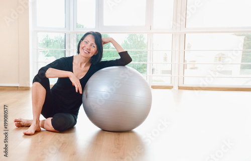 Foto  Happy senior woman resting after exercise with gray exercise ball
