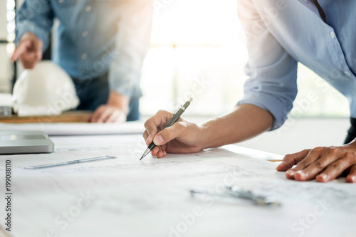 Close-up Of Person's engineer Hand Drawing Plan On Blue Print with architect equipment, Architects discussing at the table, team work and work flow construction concept