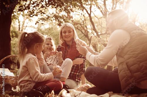 Plakat Młoda rodzina na pikniku w parku.