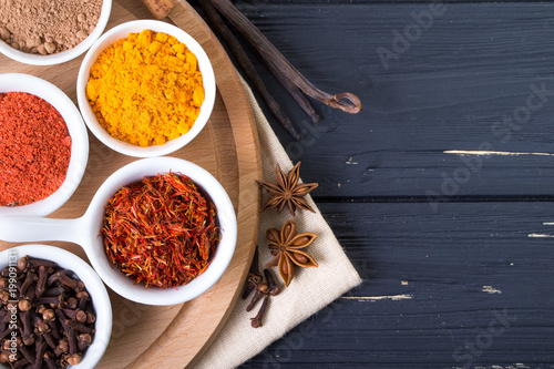 Foto op Canvas Kruiden colorful spices in ceramic containers on a dark background