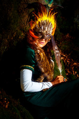 girl with shamanic feather mask and historic dress in woodland surroundings.