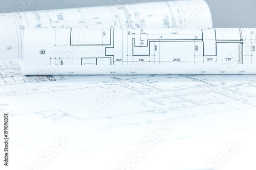 Fotografie, Obraz  architectural project drawings and blueprints rolls on desk as construction back