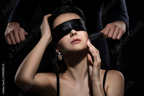 Man in suit ties a woman's eyes with a silk ribbon on black background