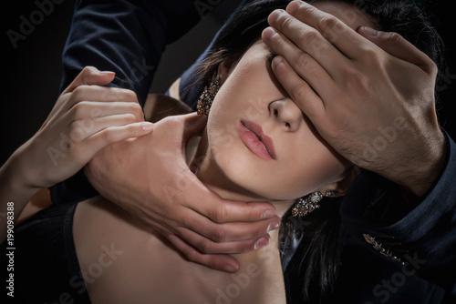 Valokuva  Man covers eyes and stifles woman on black background