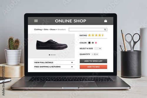 Online shop concept on laptop screen on modern desk. All screen content is designed by me. Front view