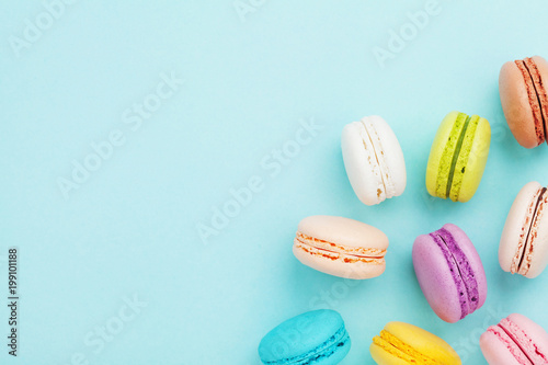 Foto op Plexiglas Dessert Tasty cake macaron or macaroon on turquoise pastel background from above. Colorful french cookies on dessert top view.
