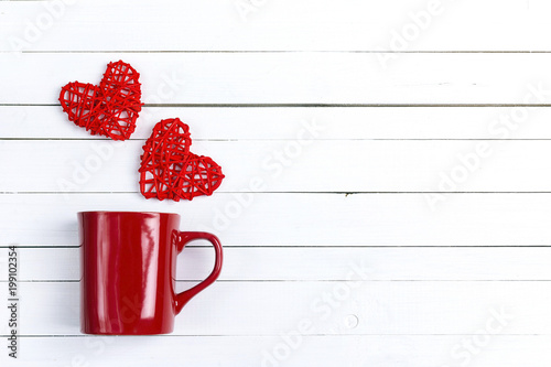 Red coffee mug with hearts coming out of it  on white wooden background.