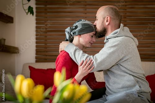 Supportive husband kissing his wife, cancer patient, after treatment in hospital Fototapet