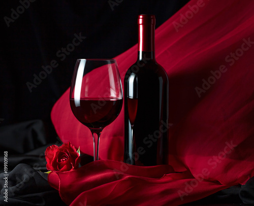 Bottle and glass of red wine .