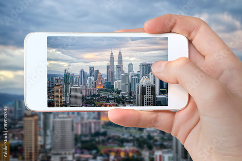 Closeup of a hand with smartphone taking a picture of Kuala Lumpur skyline, Mala Poster