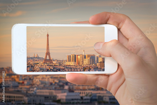 Papiers peints Paris Closeup of a hand with smartphone taking a picture of Paris with the Eiffel tower at sunset, France