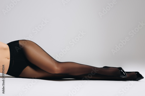 Obraz Seductive woman in black tights and shoes lying on white background - fototapety do salonu