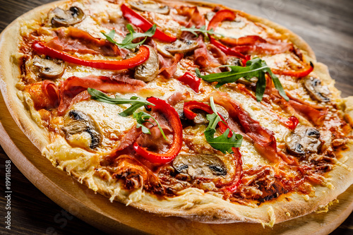 Papiers peints Jardin Pizza with ham and vegetables on wooden table