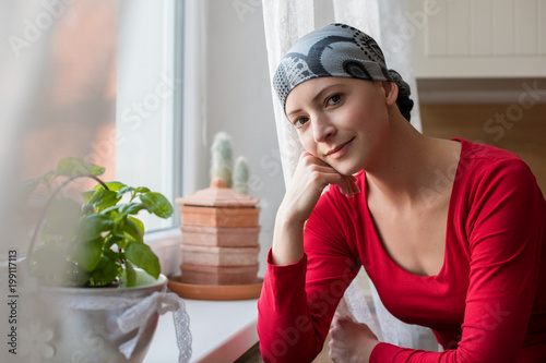 Fotografie, Obraz  Young positive adult female cancer patient sitting in the kitchen by a window, smiling and looking at the camera