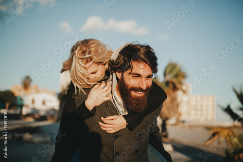 Cool indie couple having fun outdoors while he gives her a piggyback Canvas