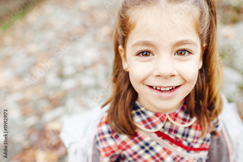 Little girl looking at the camera in the countryside in fall season
