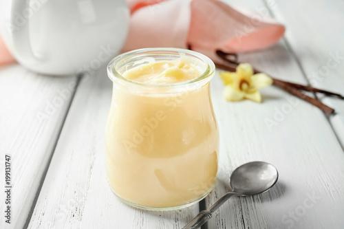 Photo  Tasty vanilla pudding in jar on wooden table