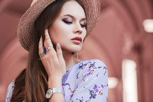 Outdoor Close Up Portrait Of Young Beautiful Fashionable Woman Posing In Street. Model Wearing Stylish Straw Boater Hat, Wrist Watch, A Lot Of Rings. Female Fashion Concept. Copy, Empty Space For Text