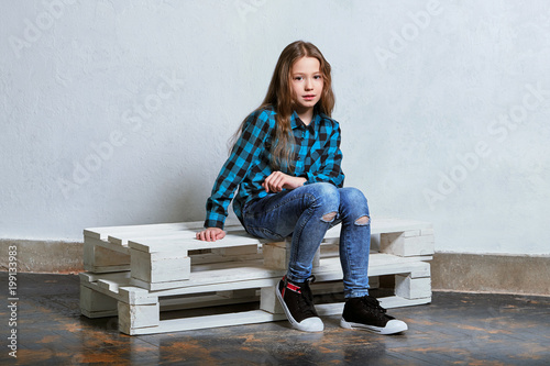 964387e0251b7 Stylish serious young girl sitting on white pallet and looking camera.  Hipster