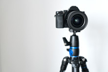 Professional Black Mirrorless Camera Stands On A Tripod Against A White Wall. Blogging And Video Photo Shooting.