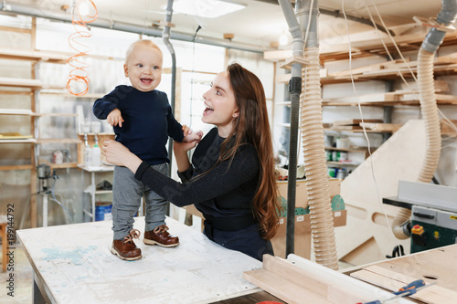 Fotografia  happy young mother with the little son in the carpenter workshop their father