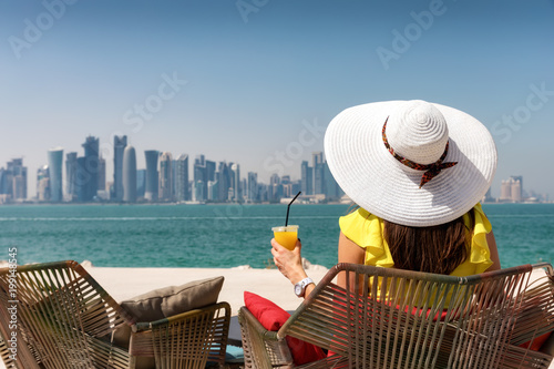 Attraktive Touristin genießt die Aussicht auf Doha in Katar bei einem erfrischen Wallpaper Mural